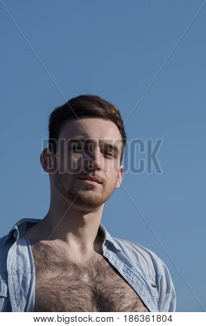 guy. Handsome young sexy caucasian model or man with bearded face and stylish hair haircut posing in unbutton shirt with naked hairy chest on sunny summer day on blue sky background. Male beauty
