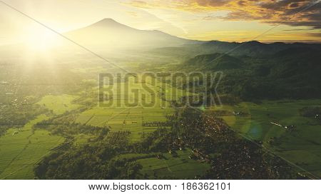 Beautiful aerial view of farmland in the village at mountain valley shot at sunrise time in Majalengka West Java Indonesia