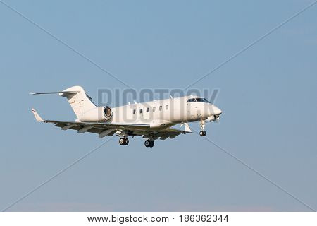 A small white business aviation aircraft landing to airport runway with the chassis released