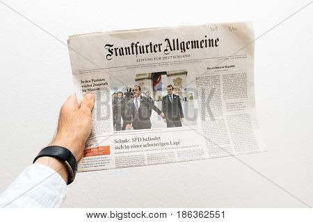 PARIS FRANCE - MAY 10 2017: Man holding frankfurter allgemeine newspaper front page against white background with the picture of the newly elected French president Emmanuel Macron the 8th President of France