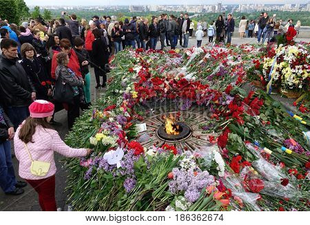 KIEV - UKRAINE - MAY 2017: Glory Park on Victory Day in Kiev. Near the eternal fire, people laid many flowers in memory of the dead soldiers during World War II