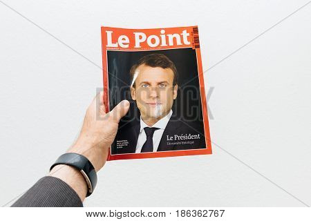 PARIS FRANCE - MAY 10 2017: Man holding Le Point magazine newspaper front page against white background with the picture of the newly elected French president Emmanuel Macron the 8th President of France
