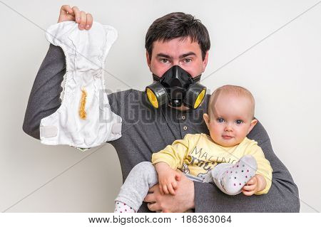 Father With Gas Mask Is Holding Dirty Diaper And Little Baby