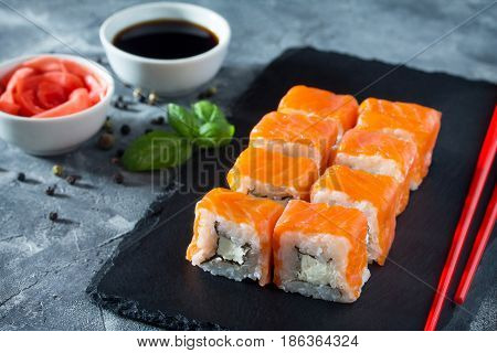 Roll Cheese Salmon On A Black Slate Board - Salmon, Soft Cheese, Nori, Rice.