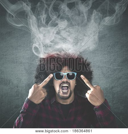 Photo of Afro man with curly hair wearing sun glasses and looks angry while showing two middle fingers with smoke coming out of his head