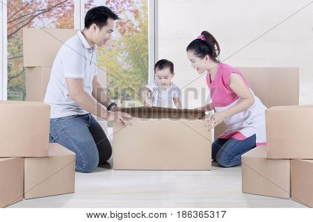 Picture of a little child with her parents unpacking boxes together in the new house