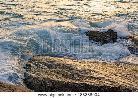 Wave over the Arpoador stone in Ipanema beach during sunset