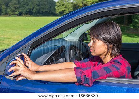 Colombian woman behind steering wheel adjusting car mirror