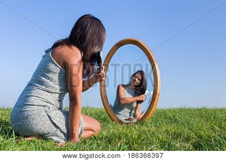 Colombian woman brushing her black hair in mirror outdoors