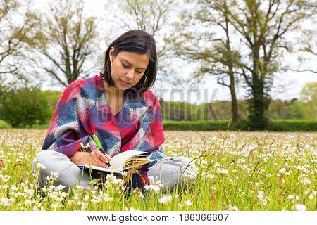 Colombian woman writing in meadow with spring flowers
