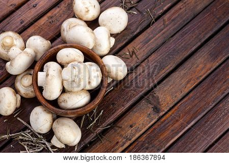 Mushrooms, champignons on wooden background. Top view. Copy space.