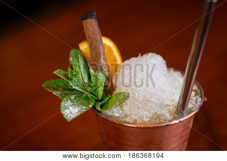 Cocktail. Mint Julep With Orange In Copper Glass And Steel Straw