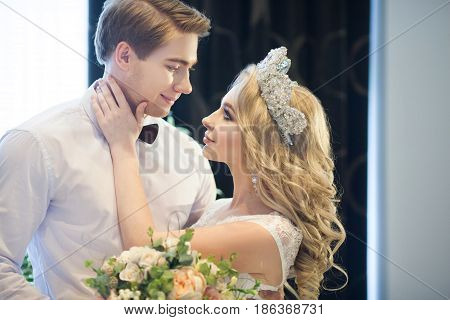 Beautiful young newlyweds in wedding dresses in a modern interior