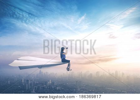 Young businesswoman sitting on a paper aeroplane while flying above a city and looking through a binoculars