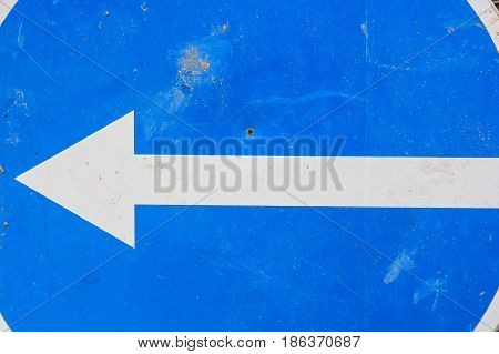 Close up road sign with white arrow to left on blue background