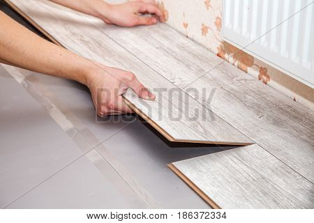 young handyman installing wooden floor in new house hands closeup