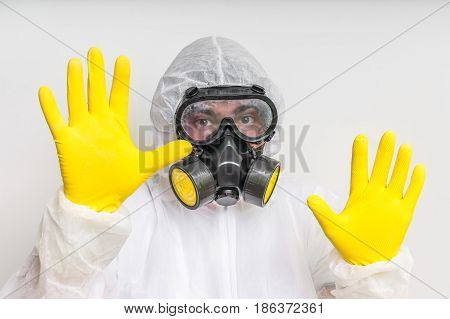 Man In Coveralls With Gas Mask Is Showing Stop Gesture