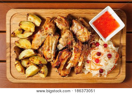 big wooden board with fried pork ribs, baked potato, hot sauce and sauerkraut, preferably served as companion for beer or other alcool drinks