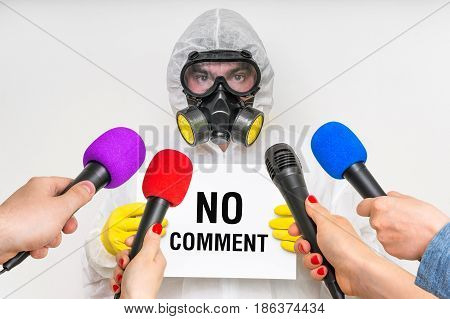 Reporters with microphones making interview with man in gas mask - journalism and broadcasting concept