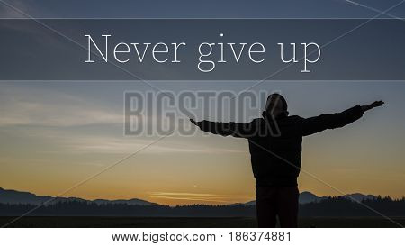 Never Give up motivational concept with the silhouette of a person with outstretched arms against a colorful rural sunset over distant hills with text.