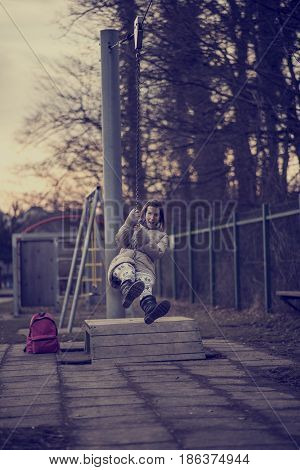 Retro effect faded and toned image of a woman having fun on a swing outdoors in a park.