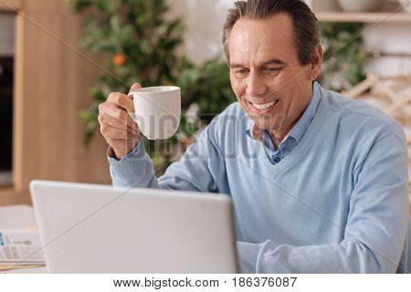 Reading morning news. Smiling glad senior man sitting in the kitchen while enjoying cup of coffee and using laptop