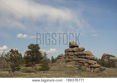 Rock cairn formation with trees and cloudy blue sky