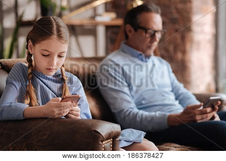 Deep in the electronic world. Addicted apathetic young girl sitting on the couch and using mobile while her grandfather surfing the Internet in the background