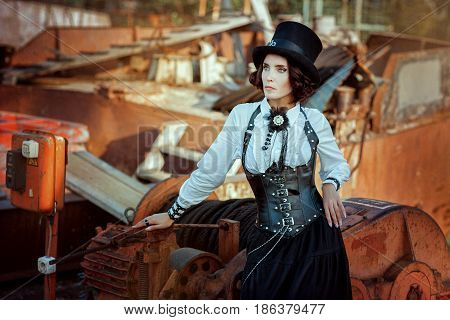 Woman dressed in a suit and a hat in a steampunk style stands next to the machines.