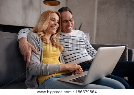 Happy family weekend. Smiling loving caring couple sitting at home and using laptop while surfing the Internet and enjoying the weekend