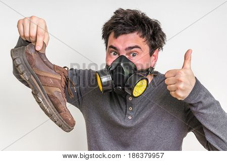 Man With Gas Mask Is Holding Stinky Shoe