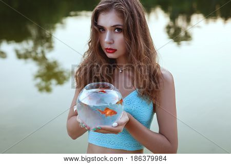 Woman is holding an aquarium with a goldfish in her hands.