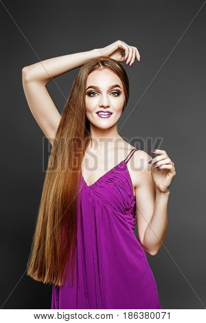 Young elegant girl in purple dress. Beauty salon. Very long hair. The concept model and beauty.