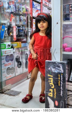 Bandar Abbas Hormozgan Province Iran - 16 april 2017: One unknown little girl about five years old is standing on doorstep of an electronics store portrait in full growth for editorial use only