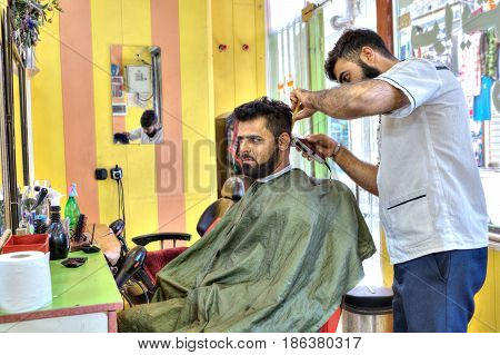 Bandar Abbas Hormozgan Province Iran - 16 april 2017: Iranian hairdresser Persian hairdresser makes a hairdo for a man.