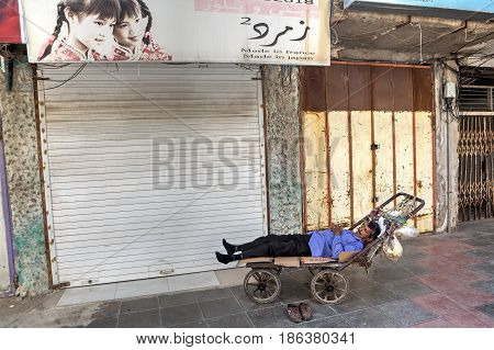 Bandar Abbas Hormozgan Province Iran - 16 april 2017: One unidentified man porter sleeping in a handcart only for editorial use.