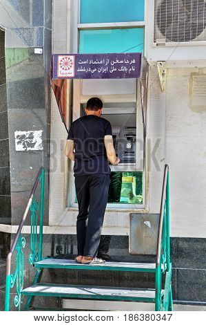 Bandar Abbas Hormozgan Province Iran - 16 april 2017: An Iranian man gets cash in an external ATM.