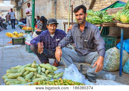 Bandar Abbas Hormozgan Province Iran - 16 april 2017: Two Iranian fruit traders are sitting on the sidewalk near their product.