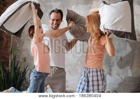 Very happy together. Playful happy delighted family amusing at home and having fun while enjoying pillow fight