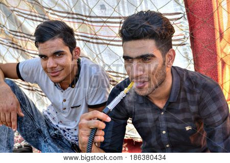 Bandar Abbas Hormozgan Province Iran - 16 april 2017: Two young people are resting in the shade under a fabric canopy one of them is smoking a hookah.