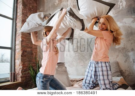 Enjoying positive weekend together. Delighted optimistic overwhelmed family amusing at home and resting while enjoying pillow fight
