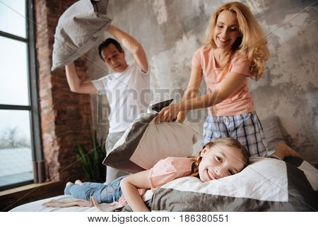 Enjoying unforgettable moments with family. Charming smiling positive girl amusing at home with parents and having fun while enjoying pillow fight