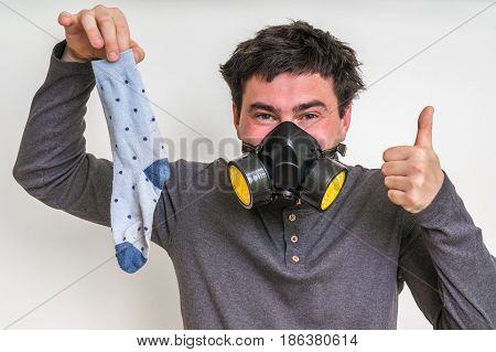 Man With Gas Mask Is Holding Stinky Sock