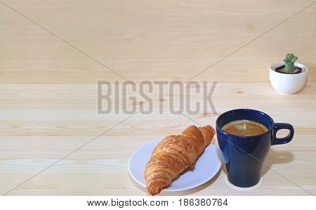 Coffee, butter croissant and a mini cactus plants on the wooden table with free space for text and design