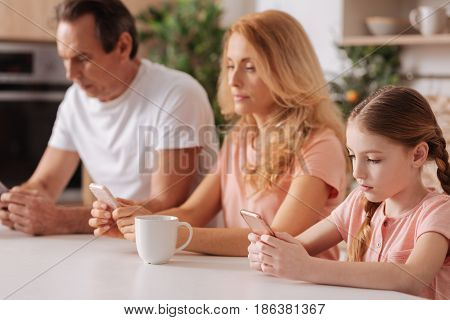 Ignoring real communication. Concentrated obsessed addicted family sitting at home and relaxing while using electronic gadgets
