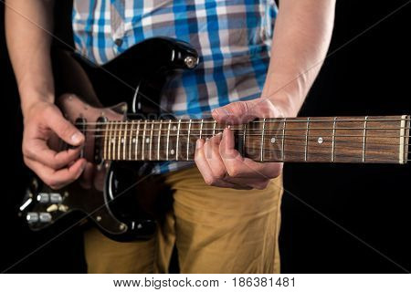 Music And Art. Electric Guitar In The Hands Of A Guitarist, On A Black Isolated Background. Playing