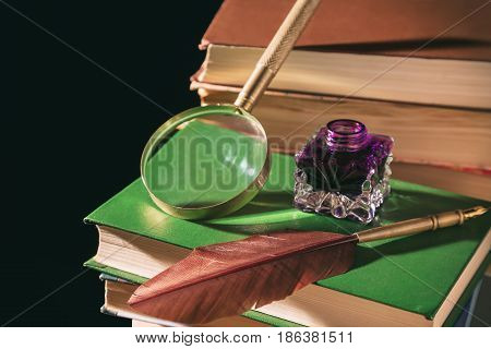 Literature concept. Inkstand with feather near magnifying glass on old books against black background.