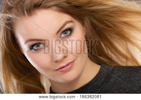 Haircare beauty hairstyling concept. Closeup portrait of young attractive blonde woman wearing dark t shirt having windblown beautiful long hair.