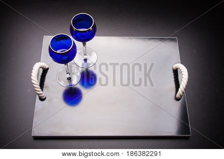 two blue glasses on a black background