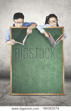 Image of two students looks serious while reading book behind a blank chalkboard